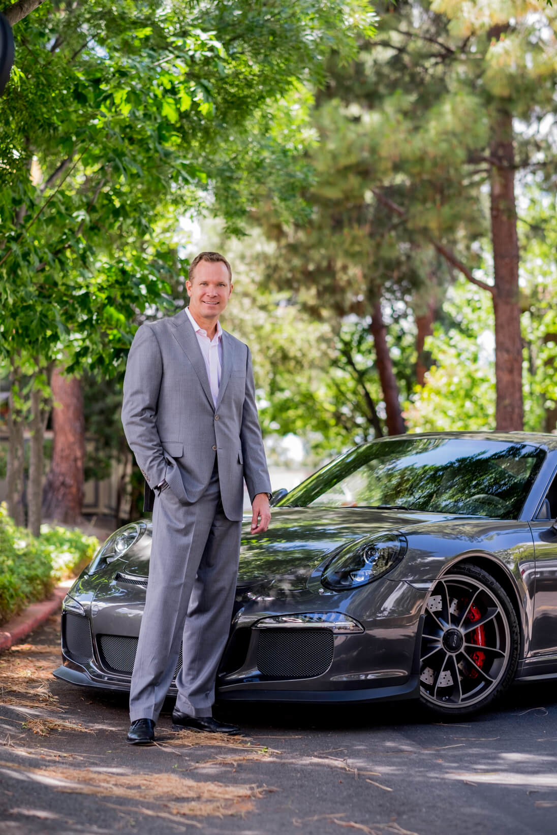 Headshot man in suit standing in front of fancy sports car.